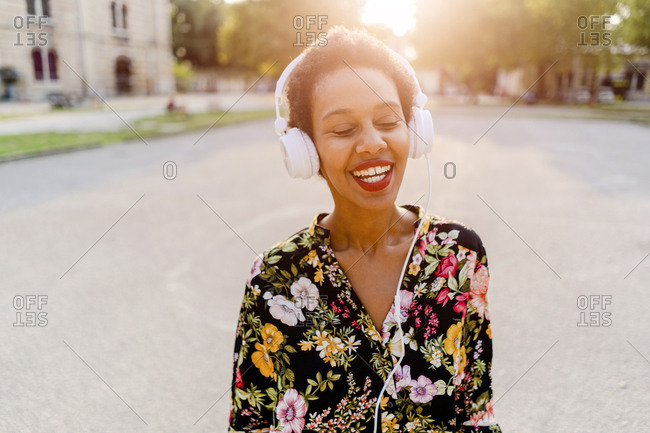 Happy fashionable young woman with headphones outdoors at sunset