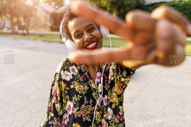 Happy fashionable young woman with headphones outdoors at sunset making victory gesture