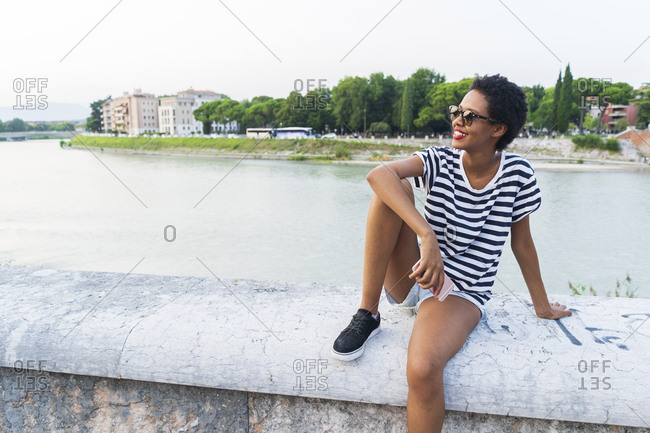 Smiling young woman wearing sunglasses sitting at the riverside