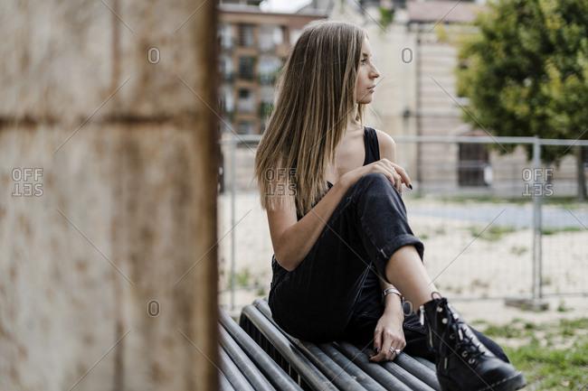 Pensive teenage girl sitting outdoors looking around
