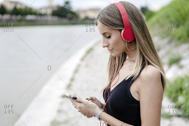 Teenage girl at the riverside wearing headphones using cell phone
