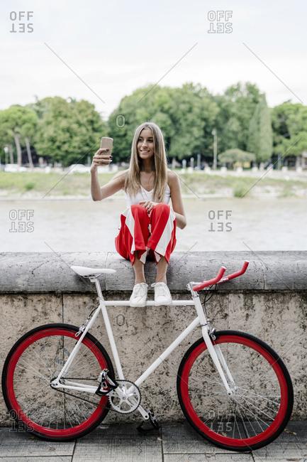 Teenage girl sitting at the riverside next to bicycle taking a selfie