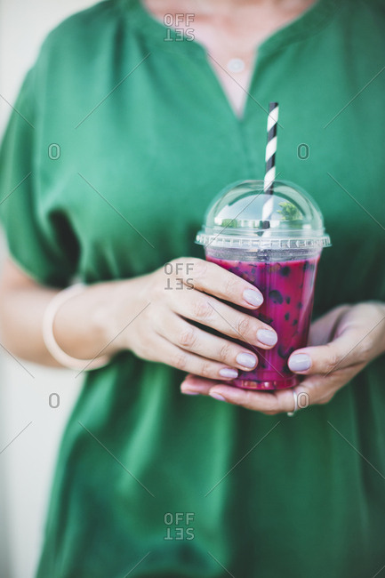Woman's hands holding plastic cup of pink smoothie- close-up