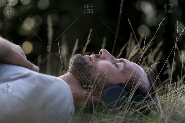 Relaxed man lying in field listening to music with headphones