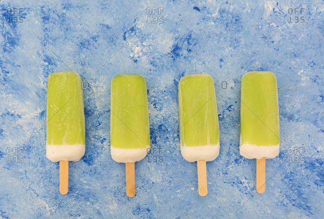 Row of four lime mint popsicles on light blue background
