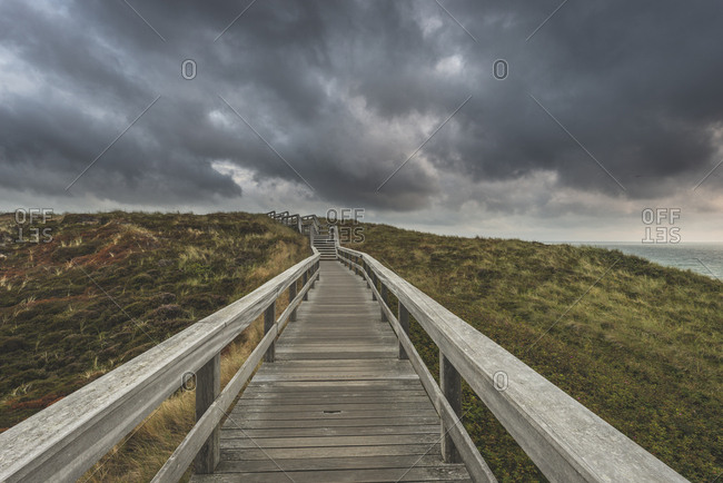 Germany- Schleswig-Holstein- Sylt- Wenningstedt- boardwalk to the beach under rain clouds