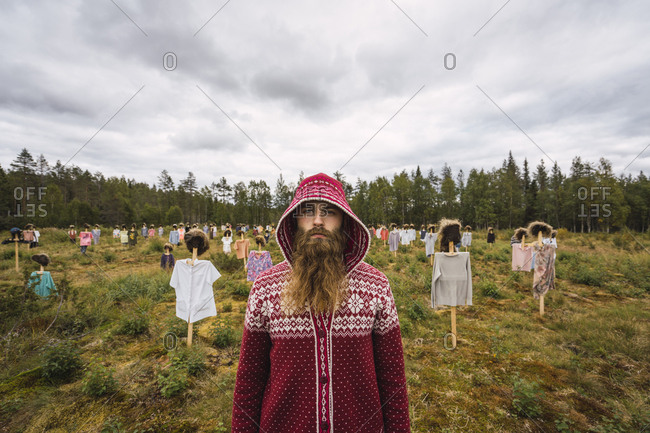 Finland-  Suomussalmi- Man standing in front of The Silent People- art project with crowd of scare crows