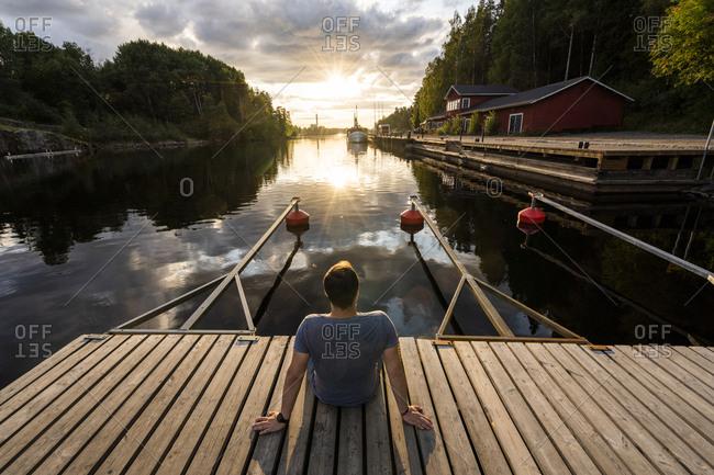 Finland- Kajaani- Man sitting on jetty- watching sunset- rear view