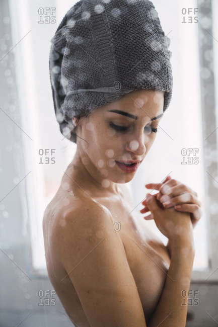 Bare-chested young woman with towel around her head at home
