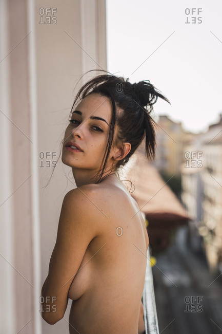 Portrait of beautiful bare-chested young woman on balcony above the city
