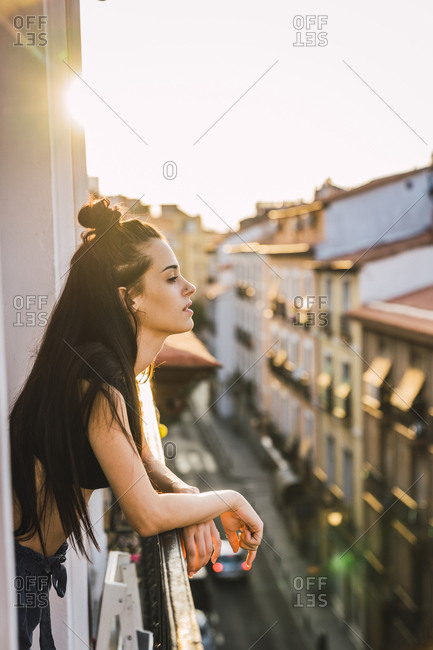 Beautiful young woman on balcony above the city at sunset