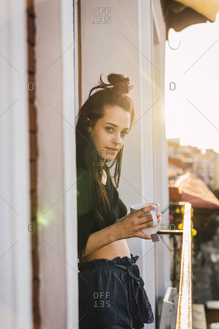 Portrait of beautiful young woman on balcony above the city at sunset with cup of tea