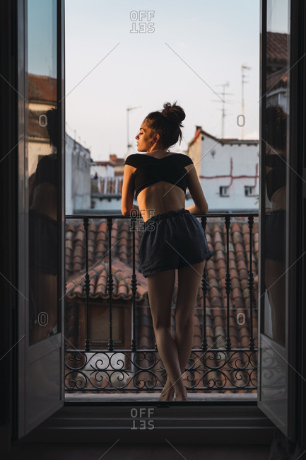 Beautiful young woman standing on balcony at sunset
