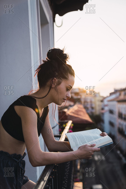 Beautiful young woman on balcony above the city at sunset reading a book