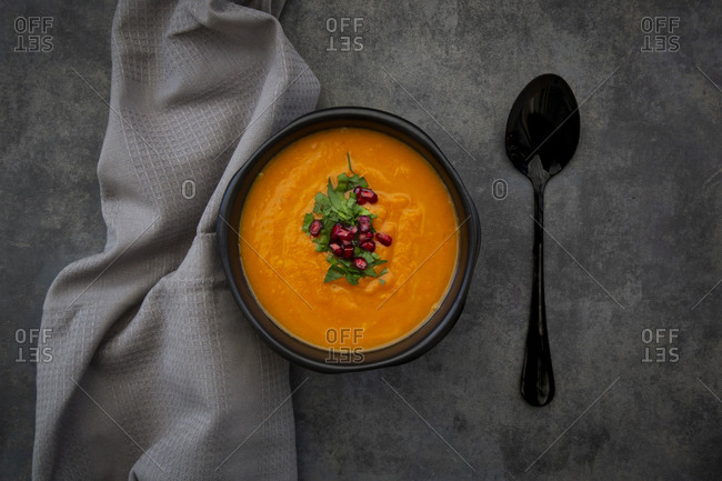 Bowl of carrot ginger coconut soup with topping of parsley and pomegranate seed