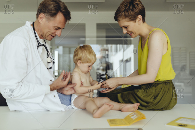 Pediatrician vaccinating toddler- injecting infant's arm- mother watching