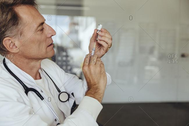 Doctor preparing injection- filling syringe