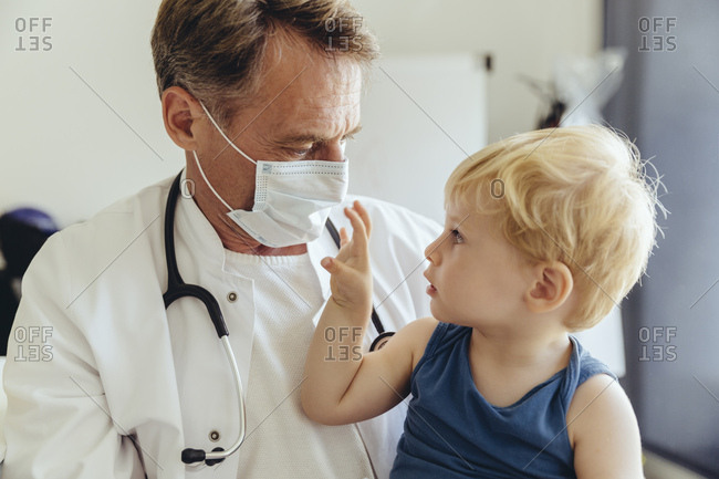 Toddler sitting on lap of pediatrician- wearing protective mask