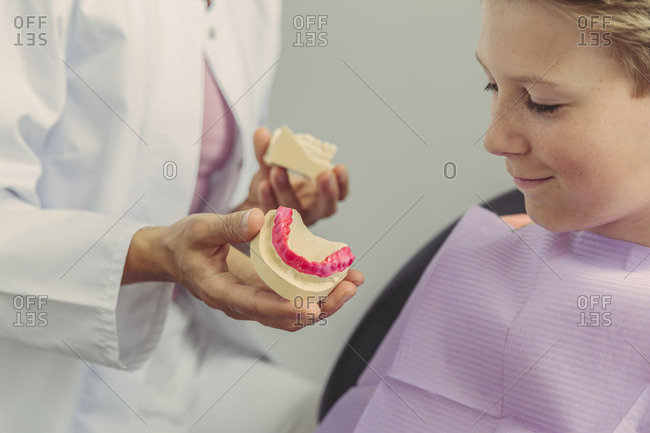 Female dentist explaining boy a tooth model