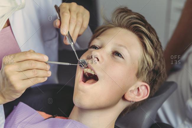 Dentist examining boy's teeth with dental instruments
