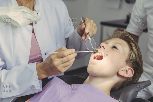Dentist examining boy\'s teeth with dental instruments