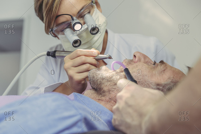 Patient getting dental treatment- dentist using dental drill and head magnifiers and light