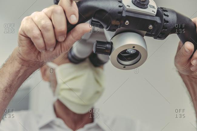 Dentist using microscope- portrait