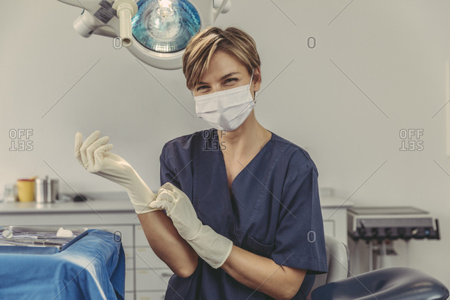 Dental surgeon wearing surgical mask- putting on surgical gloves