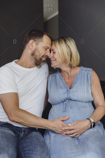 Mature man and his pregnant mature wife sitting on bed touching her belly