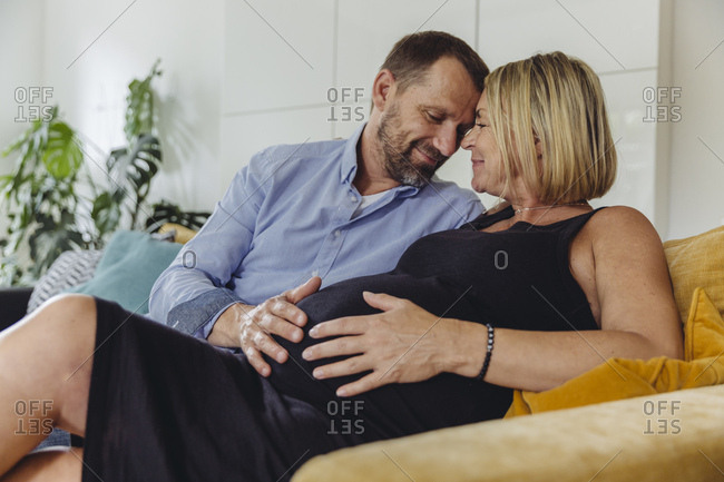 Mature man and his pregnant mature wife sitting on couch touching her belly