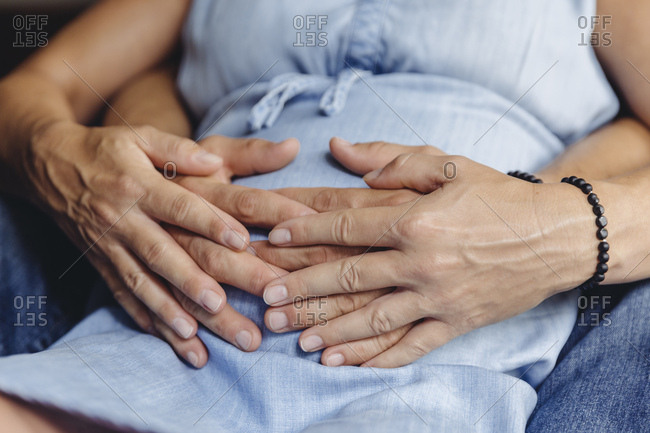 Hands of mature man and his pregnant mature wife touching her belly