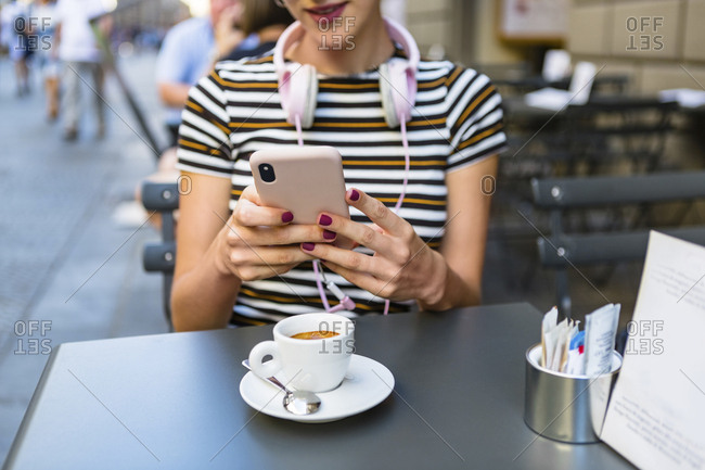 Young woman using smartphone at pavement cafe- partial view