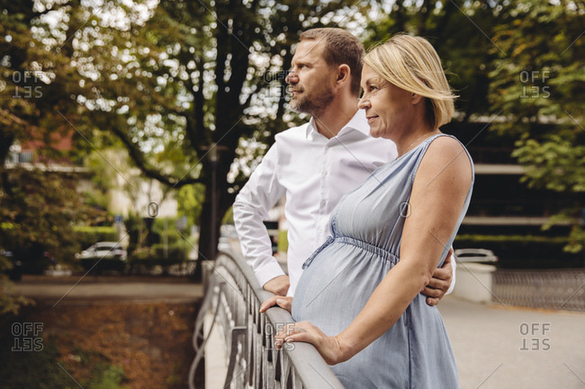 Mature pregnant couple standing at bridge in park