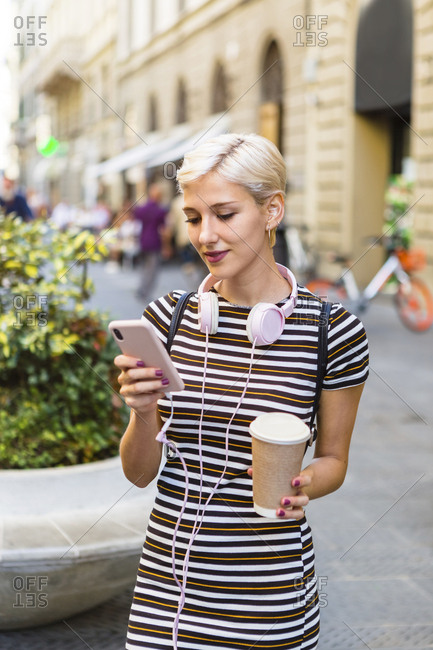 Portrait of young woman wearing striped dress standing on street with coffee to go looking at cell phone