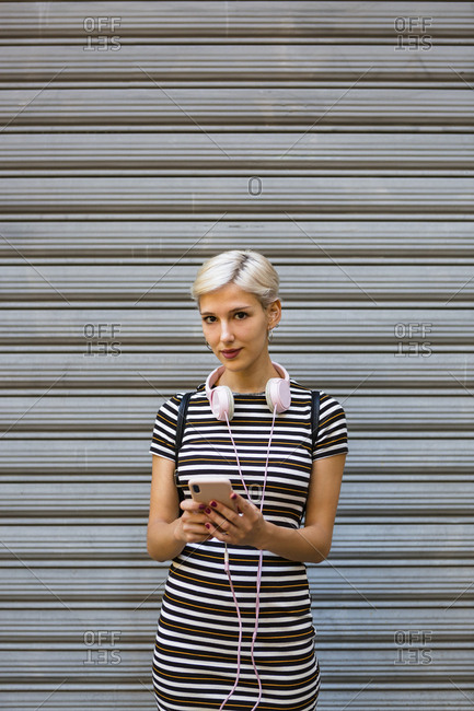 Portrait of young woman with headphones and smartphone wearing striped dress in front of roller shutter