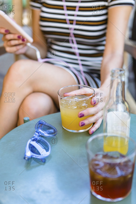 Young woman sitting at pavement cafe enjoying soft drinks- partial view
