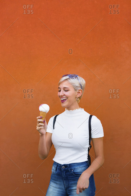 Laughing young woman with ice cream cone in front of orange background
