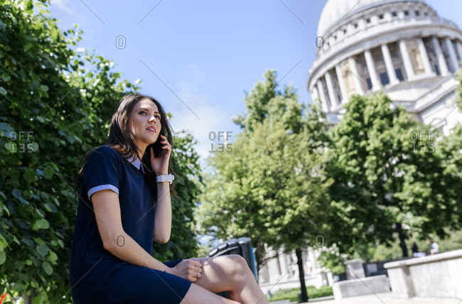 UK- London- young woman talking on the phone near St. Paul's Cathedral
