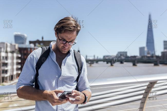 UK- London- man using his smartphone on the Millennium Bridge