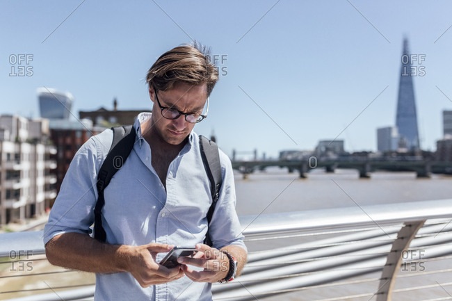 UK- London- man using his smartphone on the Millennium Bridge