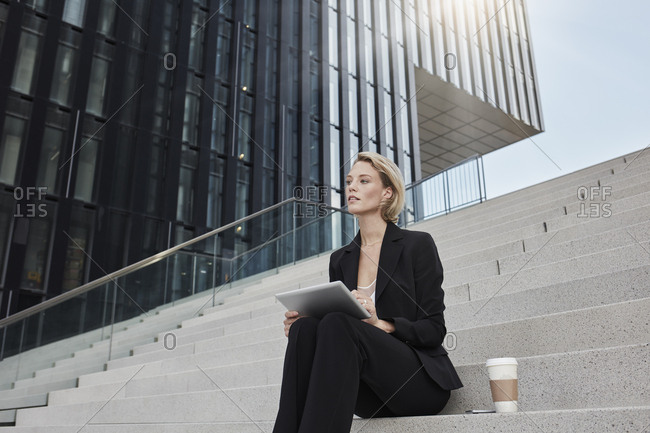 Blond businesswoman with tablet and coffee to go sitting on stairs in front of modern office building