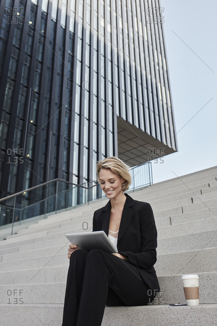 Blond businesswoman with coffee to go sitting on stairs in front of modern office building using tablet
