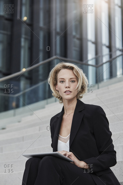 Portrait of blond young businesswoman with tablet sitting on stairs outdoors