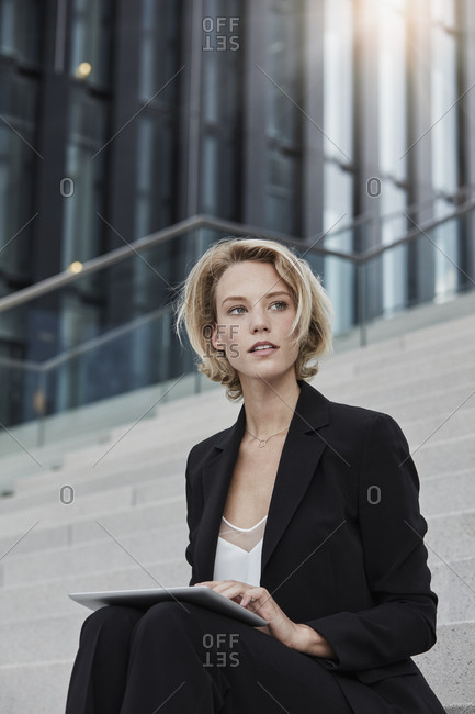 Portrait of blond businesswoman with tablet sitting on stairs outdoors