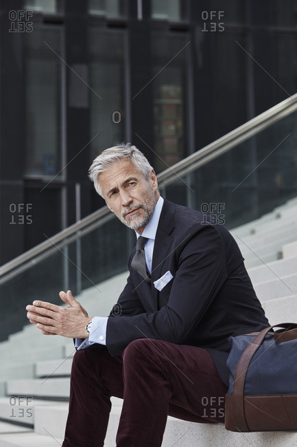 Portrait of fashionable businessman with travelling bag sitting on stairs outdoors