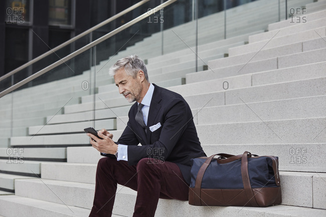 Fashionable businessman with travelling bag sitting on stairs using mobile phone