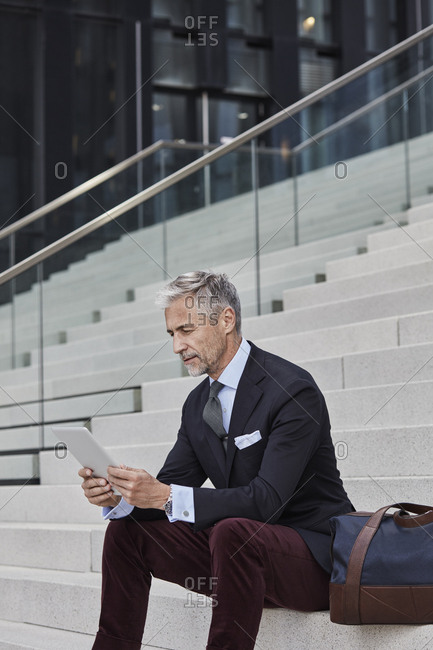 Fashionable businessman with travelling bag sitting on stairs using tablet