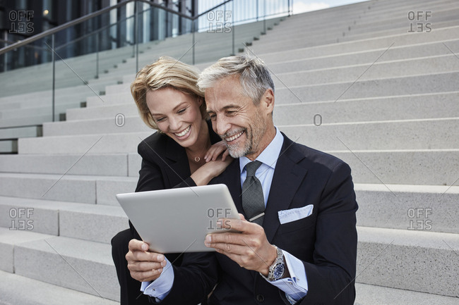 Portrait of two laughing businesspeople sitting together on stairs looking at tablet