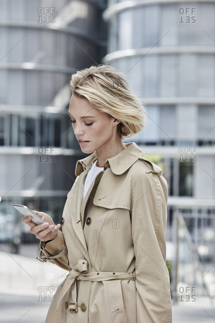 Germany- Duesseldorf- portrait of  blond businesswoman wearing beige trench coat looking at cell phone