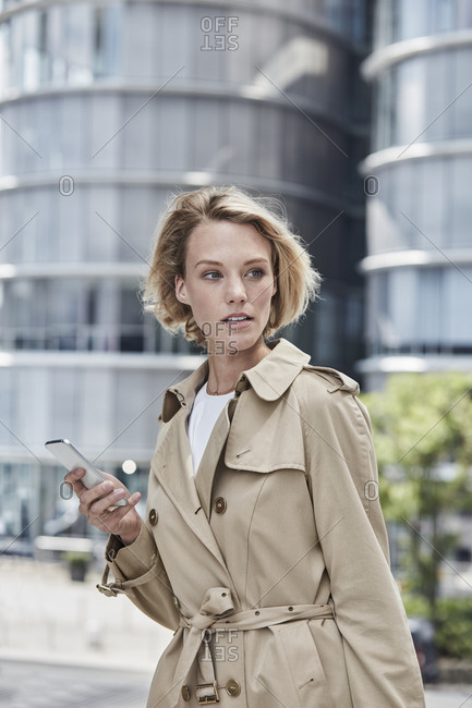 Germany- Duesseldorf- portrait of  blond young businesswoman with smartphone wearing beige trench coat